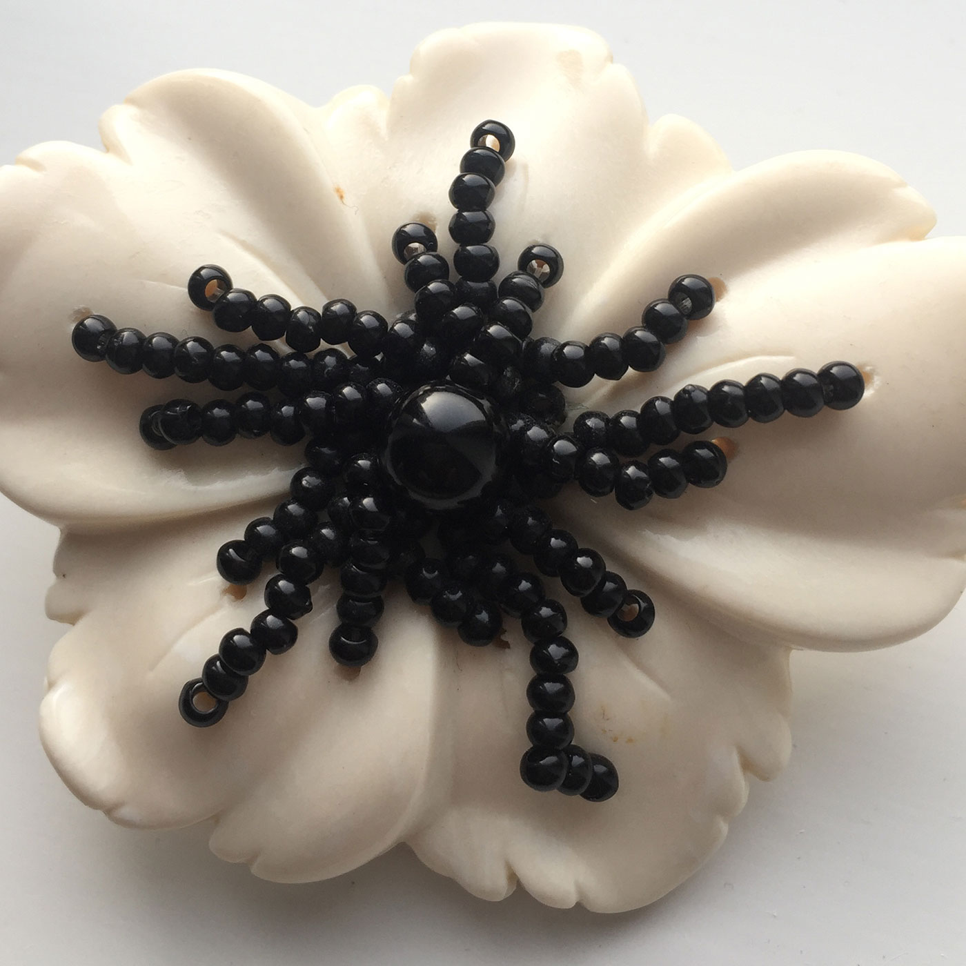 Geoffrey Beene white ceramic brooch strung with jet beading
